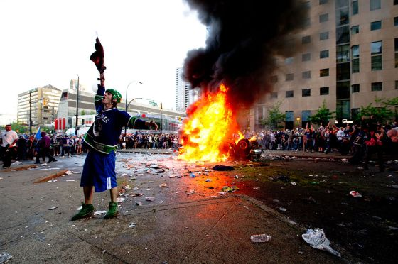 A rioter dressed in a Vancouver Canucks jersey cheers on while a car burns - Source: Wikimedia Commons, User: David Elop, Original here: http://bit.ly/1tqXdx6